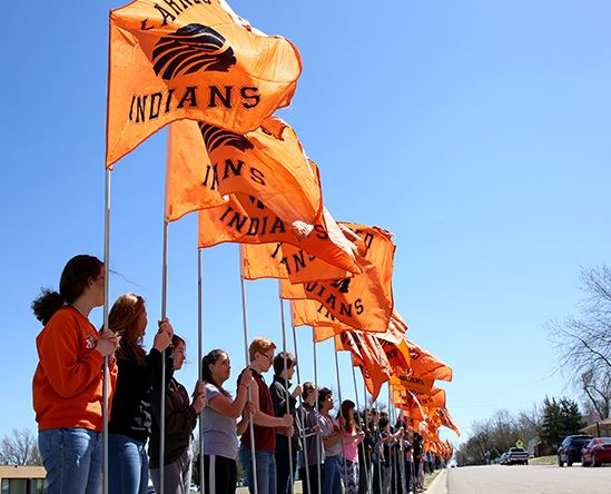 Group of teen with Larned Indians orange flags
